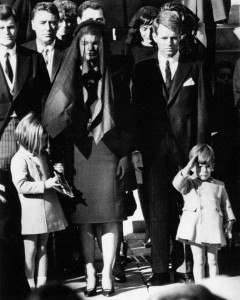 Jacqueline and children at the funeral of President John F. Kennedy. John Jr. salutes passing coffin.